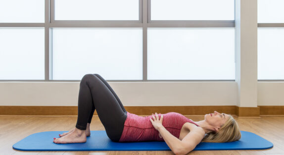 jeannie di bon is laid on a yoga mat with her knees bent