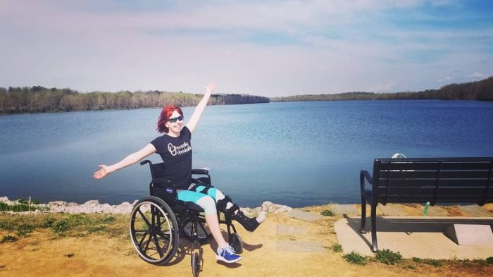 Jamie smiles in her wheelchair with arms outstretched