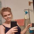 genevieve is taking a selfie, while holding an IV pole