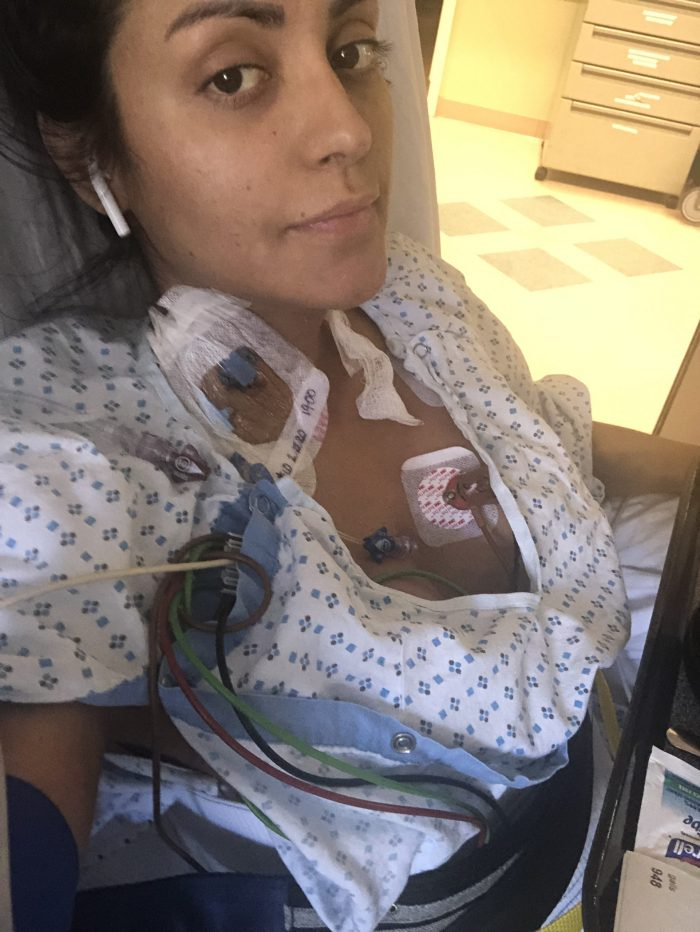Claudia sits in a hospital bed with wires attached to her chest