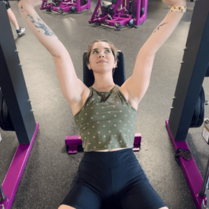 kayla is laid on a gym bench and performing a bench press, her elbows hyperextended