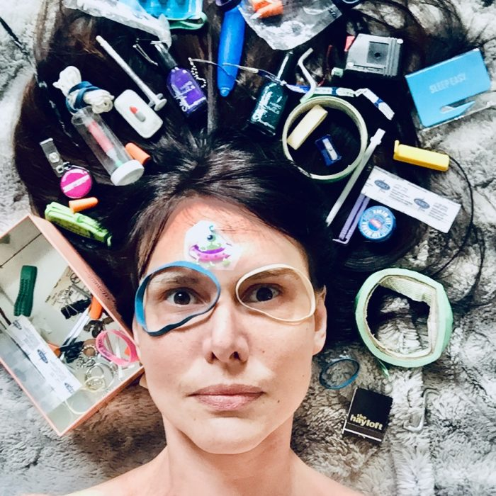 lisa is laid on the floor with her hair spread out behind her, and different cosmetic products spread on top