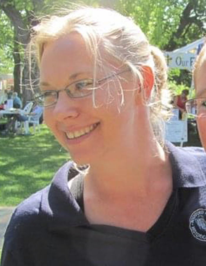 a blonde woman with glasses shot from the site, smiling