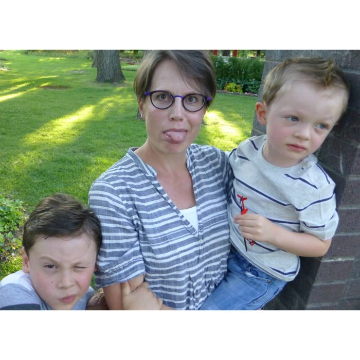 Rebecca sticks her tongue out at the camera, holding one son and another son is winking beside her