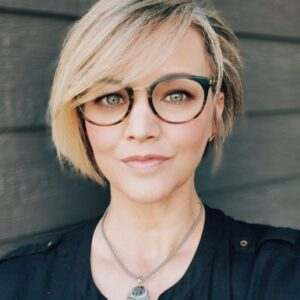 Rebekah has blonde cropped hair and looks into the camera, wearing tortoiseshell glasses, a black shirt, and a dreamcatcher necklace.