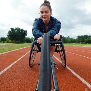 Abby sits in her adaptive racing wheelchair on the track.