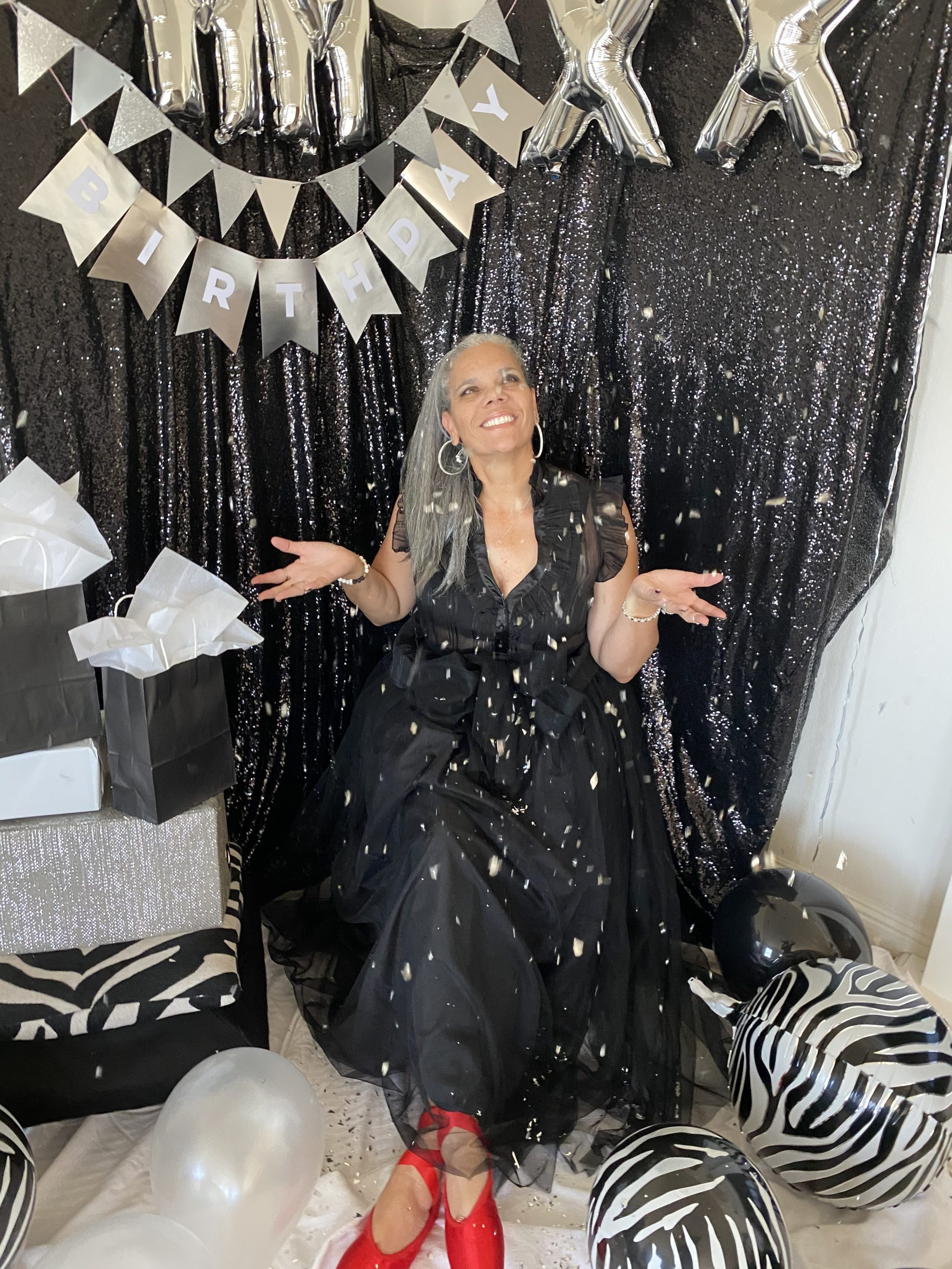 Angie wears a black dress and red shoes, and is surrounded by birthday decorations, glitter, and on the floor sits a zebra ball!