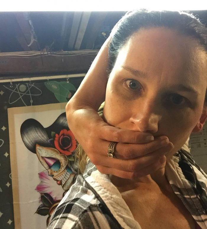 Sarah looks into the camera. Her arm is behind her head, her hand cupping her face. Behind her is artwork.