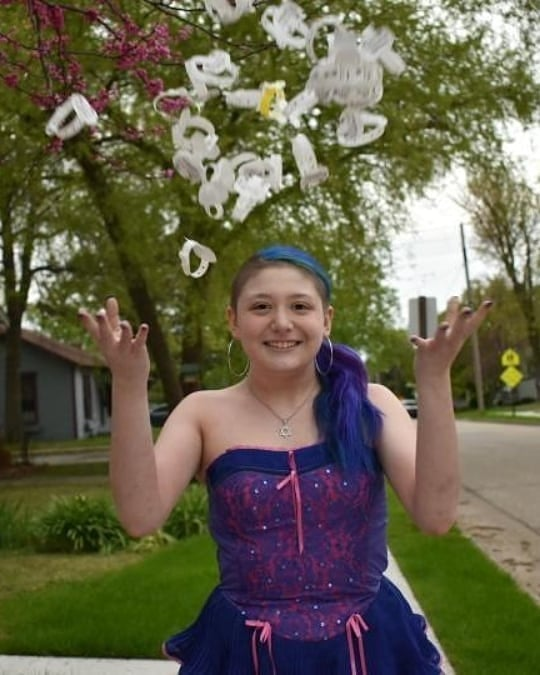 Lena standing outside in front of a sidewalk with trees, smiling and tossing her hospital bands into the air. She is wearing a pink and purple strapless dress and a necklace.