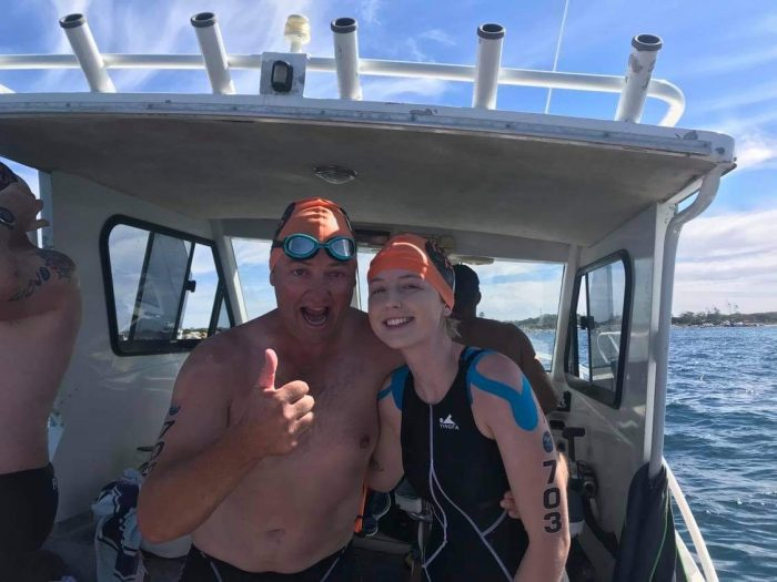 Alisha wears a swim cap and KT tape on her shoulder, standing on a boat with a person holding up their thumb.