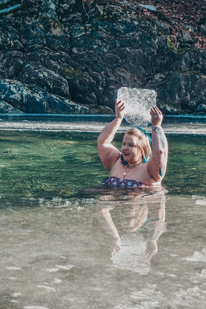Carin holding ice above her head in the water