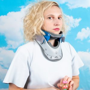 1st image is a hybrid contemporary and Renaissance-style portrait, a woman with a calm dignified expression regarding the viewer, wearing a crisp white neoprene dress and a cervical collar evoking a European ruff. The background, clouds and blue sky. In her hands, a little toy brain in an astronaut helmet.
