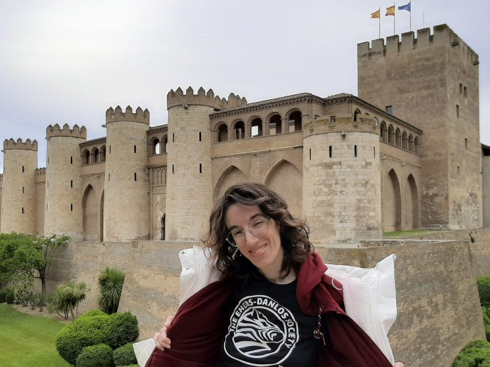 Smiling thin and pale woman with wavy brown hair and glasses, with her hoodie opened, showing the Circle with the Zebra of the EDS Society shirt. The shirt is black and the logo is white. The hoodie is maroon. She is in front of a castle with the highest tower with three flags, the Aragon, the Spanish and the European ones. The castle is surrounded by a moat full of grass and bushes. The castle is a fortified medieval palace built during the second half of the 11th century in Mudejar Architecture of Aragon, a World Heritage Site