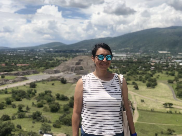 Ximena stands in a scenic area wearing a striped shirt and sunglasses