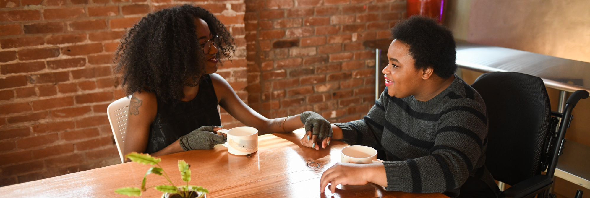 A slightly overhead perspective of two disabled Black women (one wearing compression gloves, and the other in a power wheelchair) holding hands while on sitting across from each other on a coffee date.